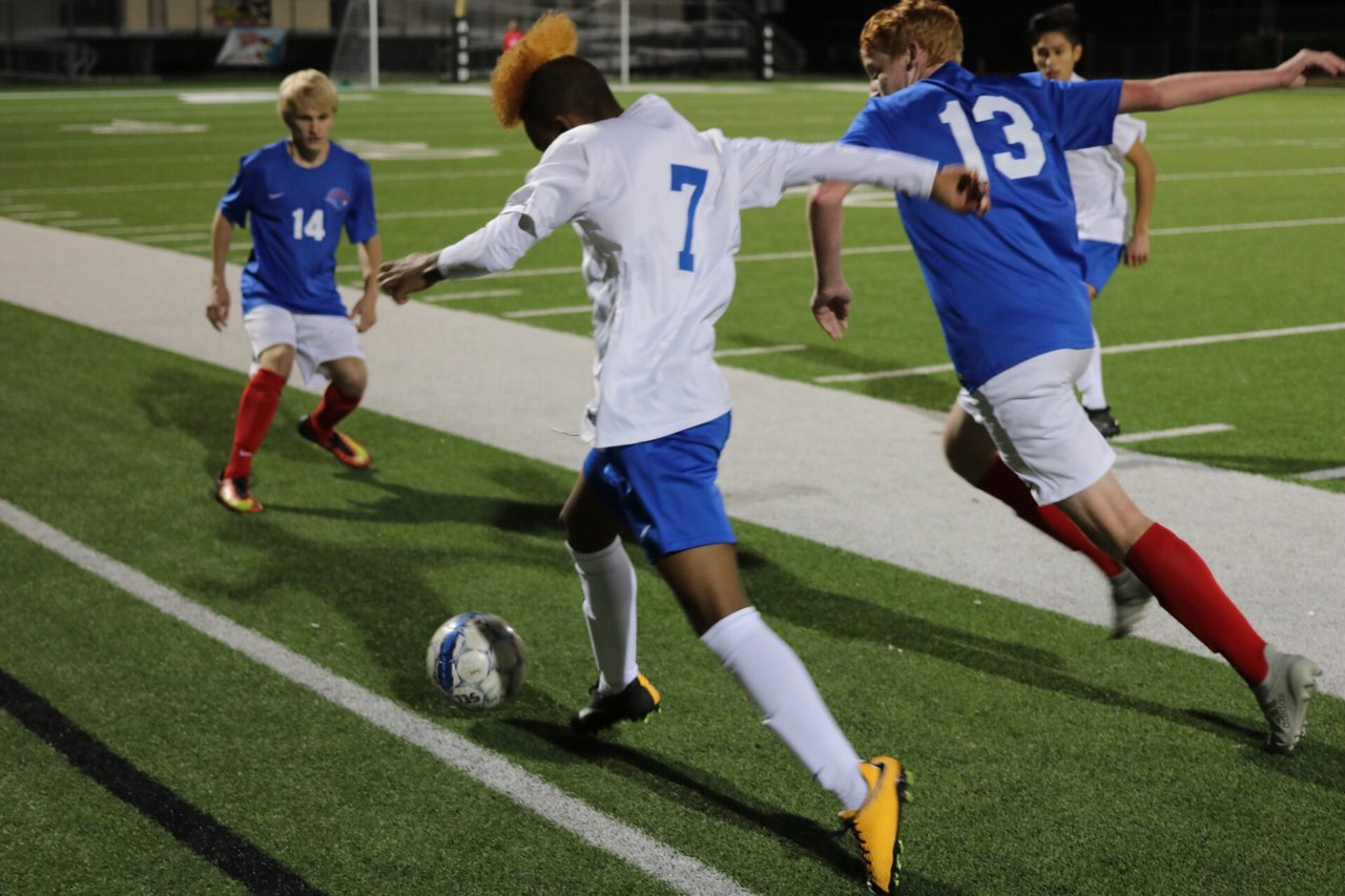 Yoni Southwick pushes the ball past two Leander defenders during tonight's 2-0 varsity loss to the Lions tonight at House Park. Photo by J. R. Cardenas.
