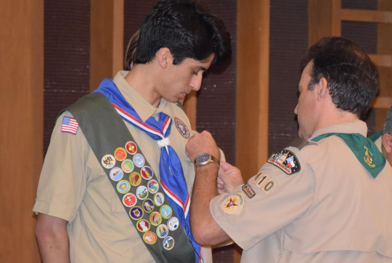Trinity University freshman Nikhil Joyce (Mac Class of 2017) receives his Eagle pin at the Eagle Scout Court of Honor he shared with five other longtime Troop 410 scout mates. Photo courtesy of Marc Vandament.