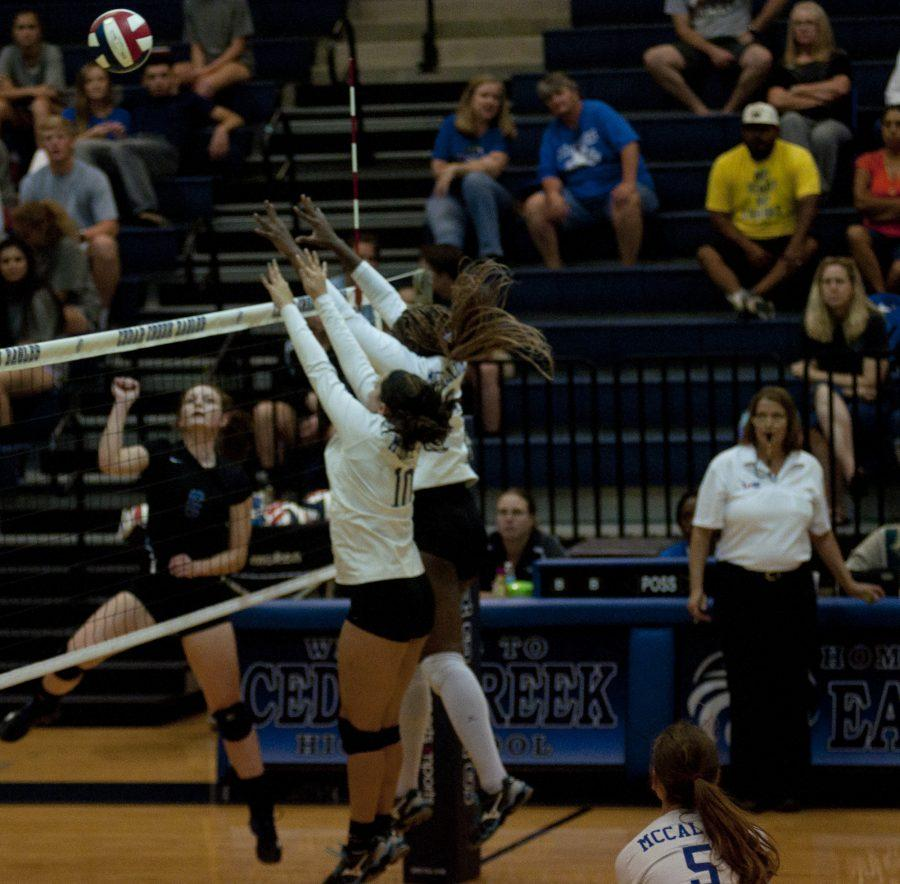 Two volleyball players get ready to block the ball