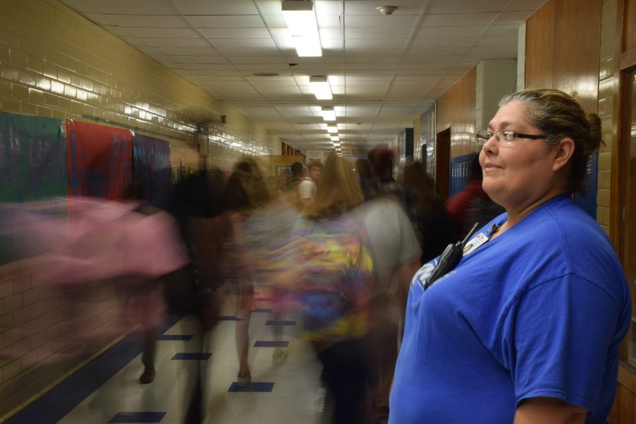 """LEFT: Officer Georgia Gonzalez watches as students pass through the main hallway during passing period. """"I really like interacting with the students as they go to class."""" Gonzalez said.  Photo by Gregory James."""