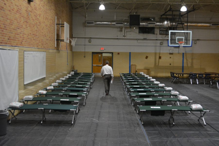 Principal Mike Garrison walks through the rows of green cots that he helped set up. Photo by Dave Winter.