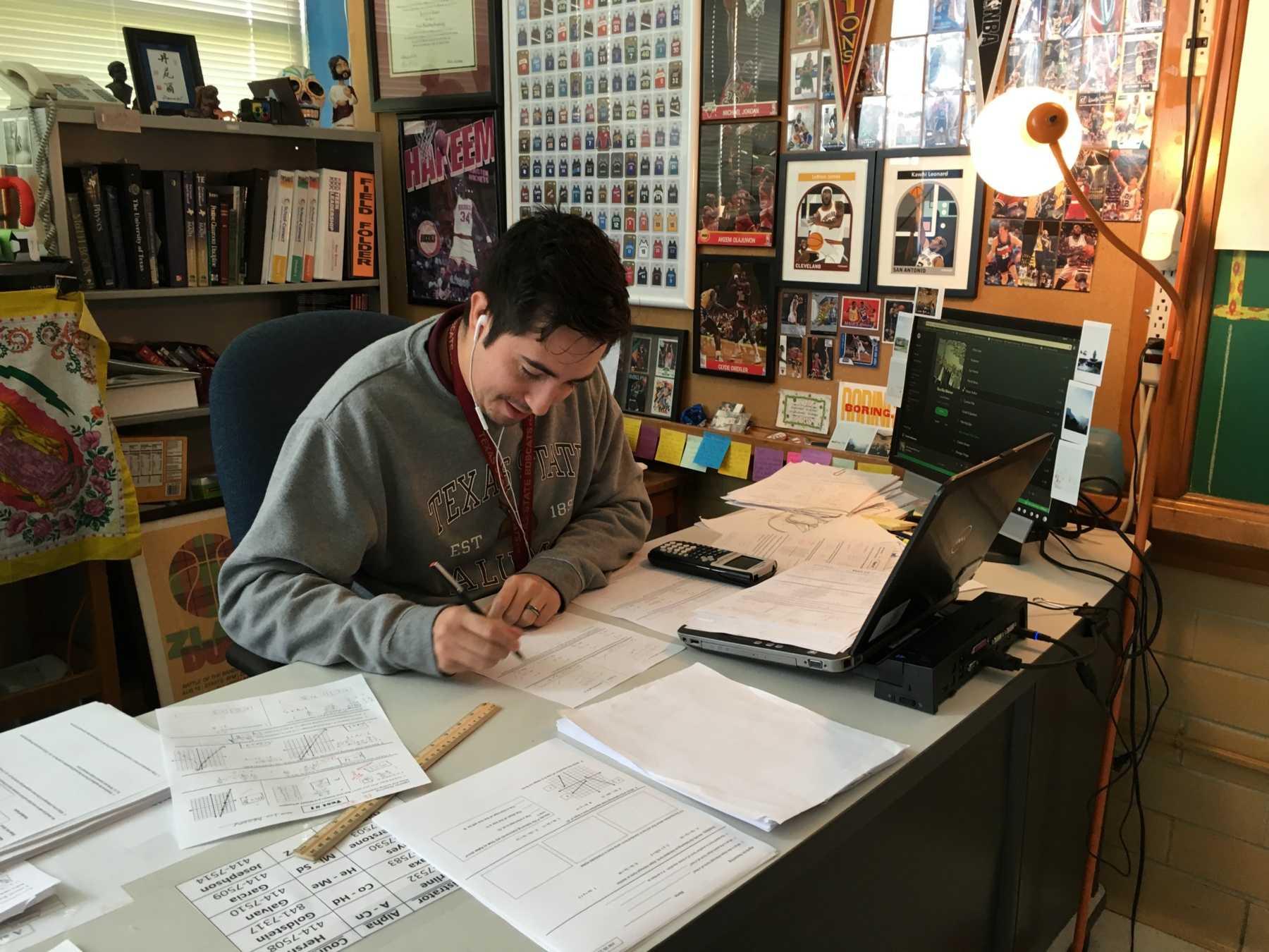 New teacher Daniel Vega grades papers at his desk. Photo by Max Rhodes.