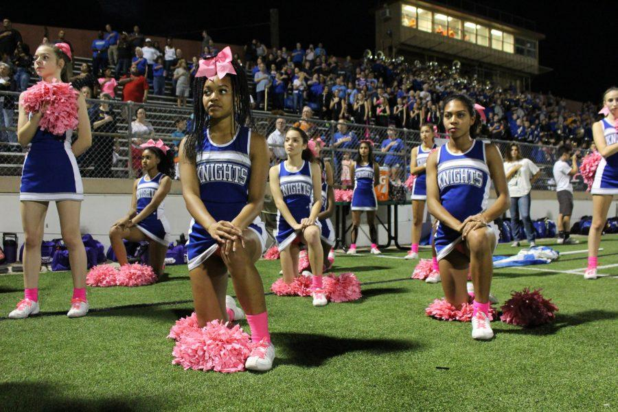 TAKING A STAND BY KNEELING DOWN:  Members of the McCallum cheerleaders, for the 4th week, kneeled during the pledge of allegiance at the Knights win over the Crockett Cougars 55-0. The cheerleaders are participating in the #Takeaknee movement that has swept the NFL in recent weeks. photo by Madison Olsen