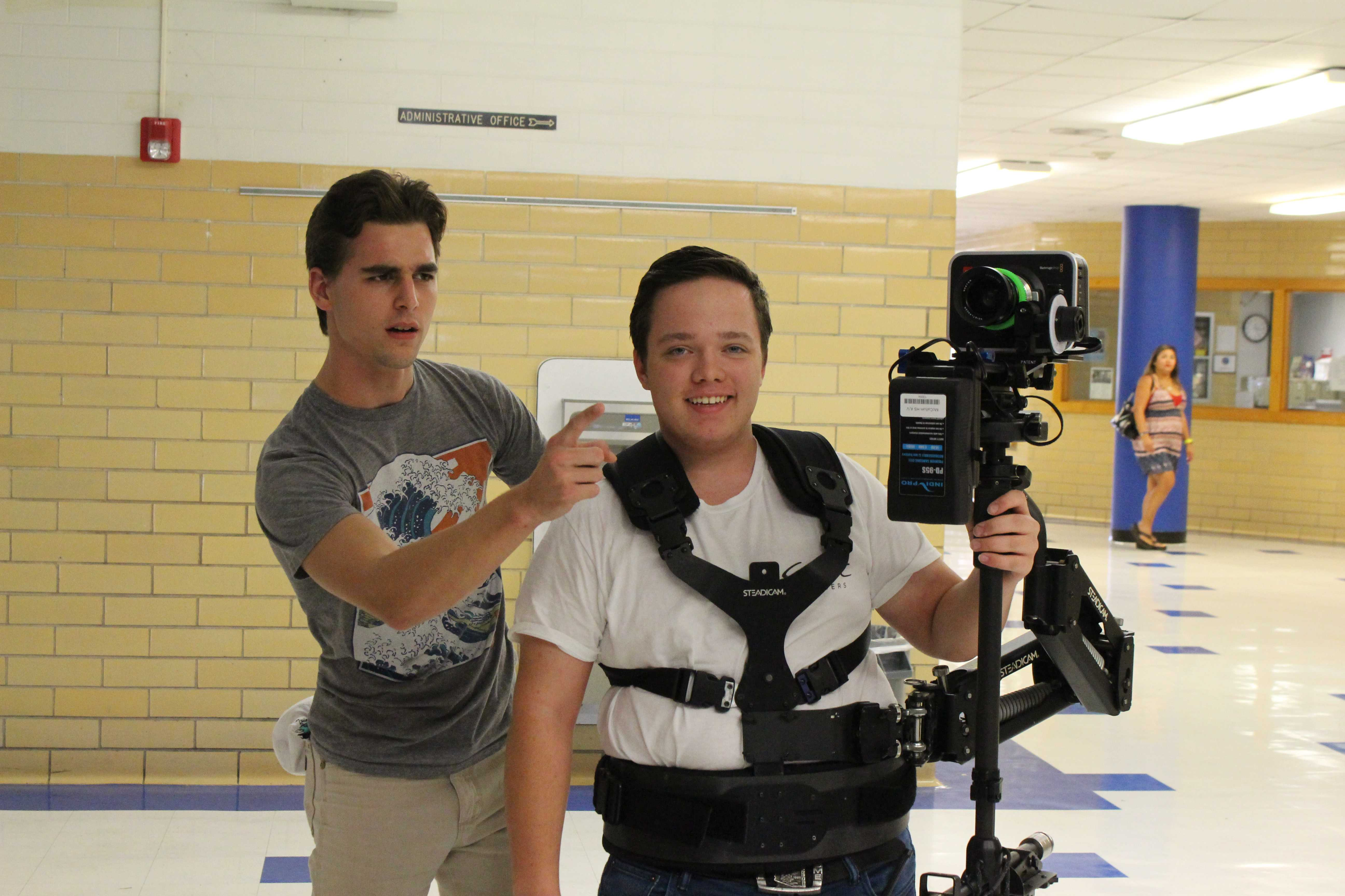 Senior William Magnuson helps junior Noah Powell use a steady cam while filming the Taco Shack Pep Rally.