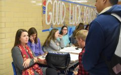 Ms. Watson oversees the homecoming sales table at lunch today in the main hallway. Photo by Abby Robison.