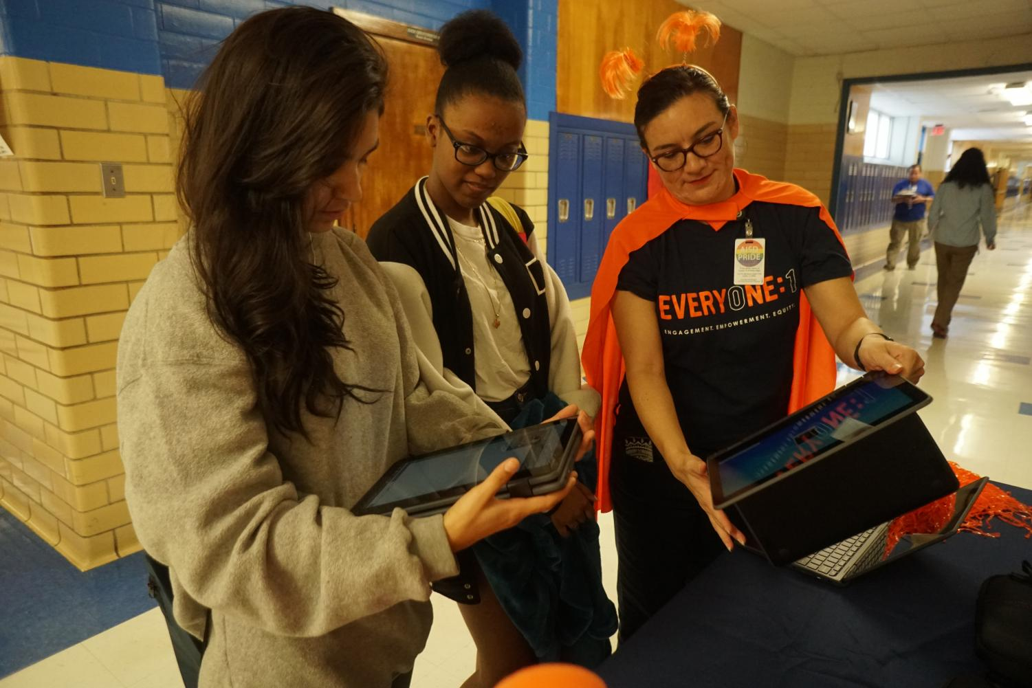 Sophomores Desaray Trevino and Aaliyah Cruz talk to AISD technology design coach Rita Fennelly-Atkinson about the Chromebooks students will receive in January. During lunch last week, Fennelly-Atkinson demonstrated the new laptops and how to use them. Photo by Maddie Doran.