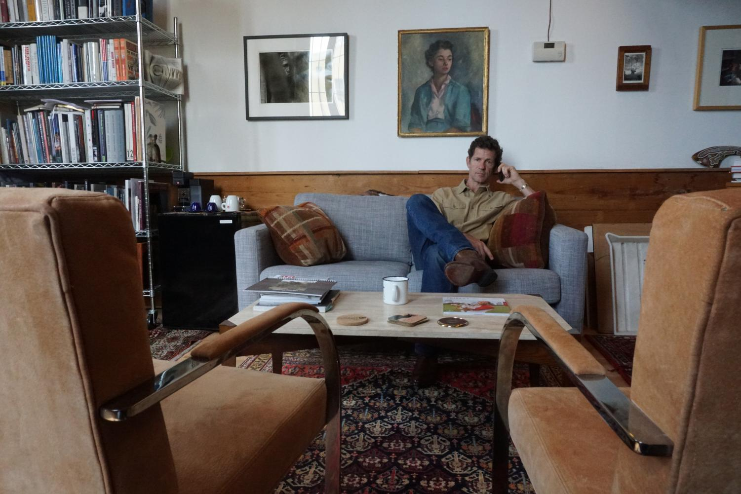 This project depicts my father at his place of work and shows the connection that he maintains with the rest of the family through phone and also through the photos and paintings of family members that line the walls of the office. Each of the photos depicting my father with pictures in the background include members of the family. The one of him at the window shows me and my brother, the one of him at his desk shows my mother in the background, and the one of him on the couch shows an older relative in the painting. I feel the strongest of these pictures is the one of him on the couch with the chairs in the foreground. This one has the strongest composition and makes the best use of the space in his office to create a compelling image, it also features the painting of the woman who is a family member hanging right above his head. Photo by Jordan Langmore. Selected for Work+Family archive.