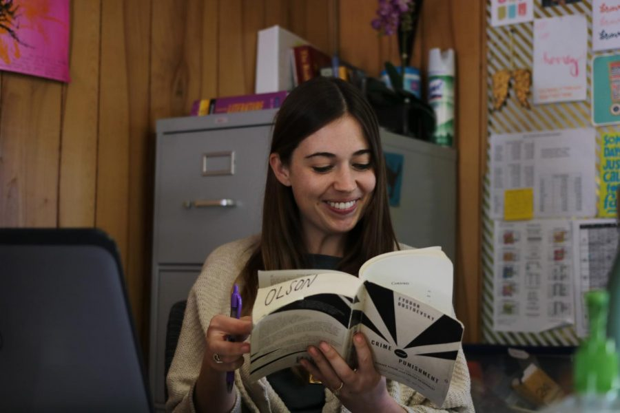 "Dana Olson sits at her desk, reading from one of her favorite books, Crime and Punishment by Fyodor Dostoevsky.  ""I like 19th-century Russian literature a lot,"" Olson said. ""'Crime and Punishment [is] one of my favorites, so I love being able to teach that.""  Photo by Joseph Cardenas."