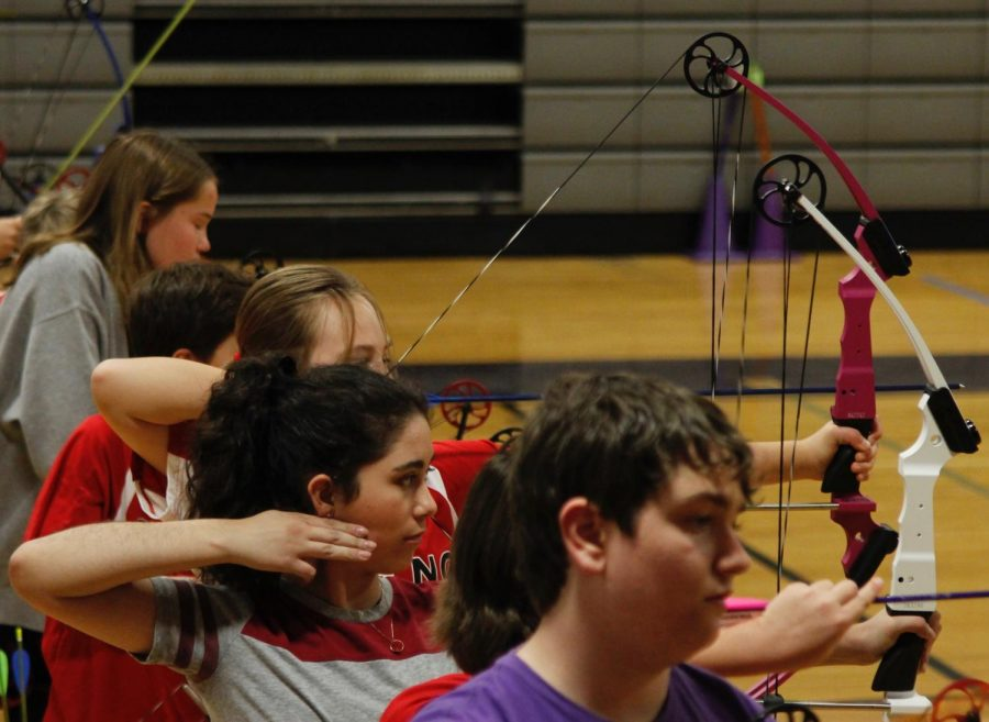 Freshman Mariana Torres DeLine releases an arrow at the National Archery in the Schools Program tournament at Lamar Middle School on Jan. 28. She qualified for the state meet at the event by scoring 266 out of a possible 300 points. While she is very competitive at archery, she does not use her involvement of the sport to earn off-campus PE credit. Photo by Kristen Tibbetts.