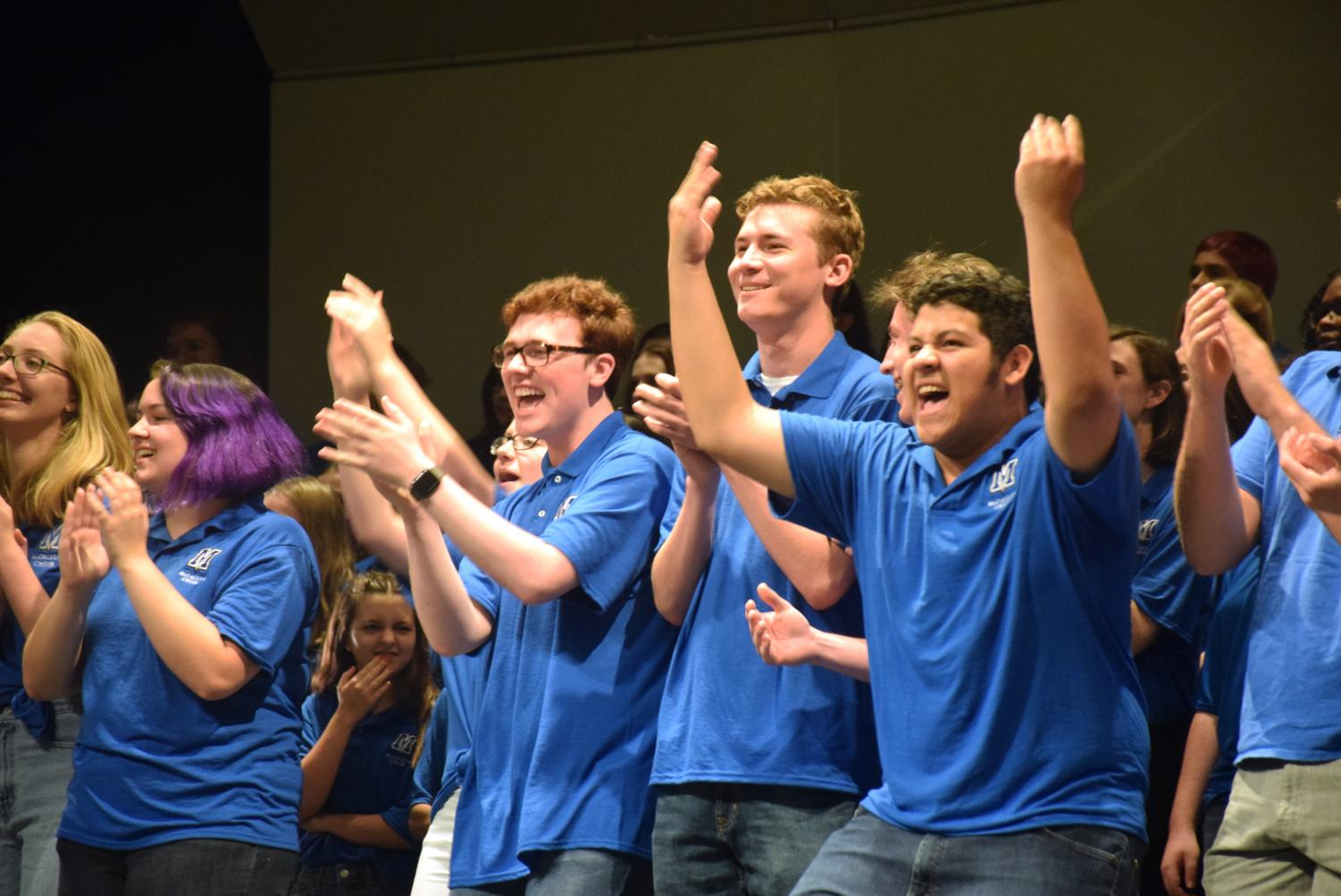 Seniors Tryston Davis (left) and Wilson Caballero (right) cheer on McCallum Choir alumni as they join the current choir onstage. At the end of the last concert, former Mac choir members are invited to sing