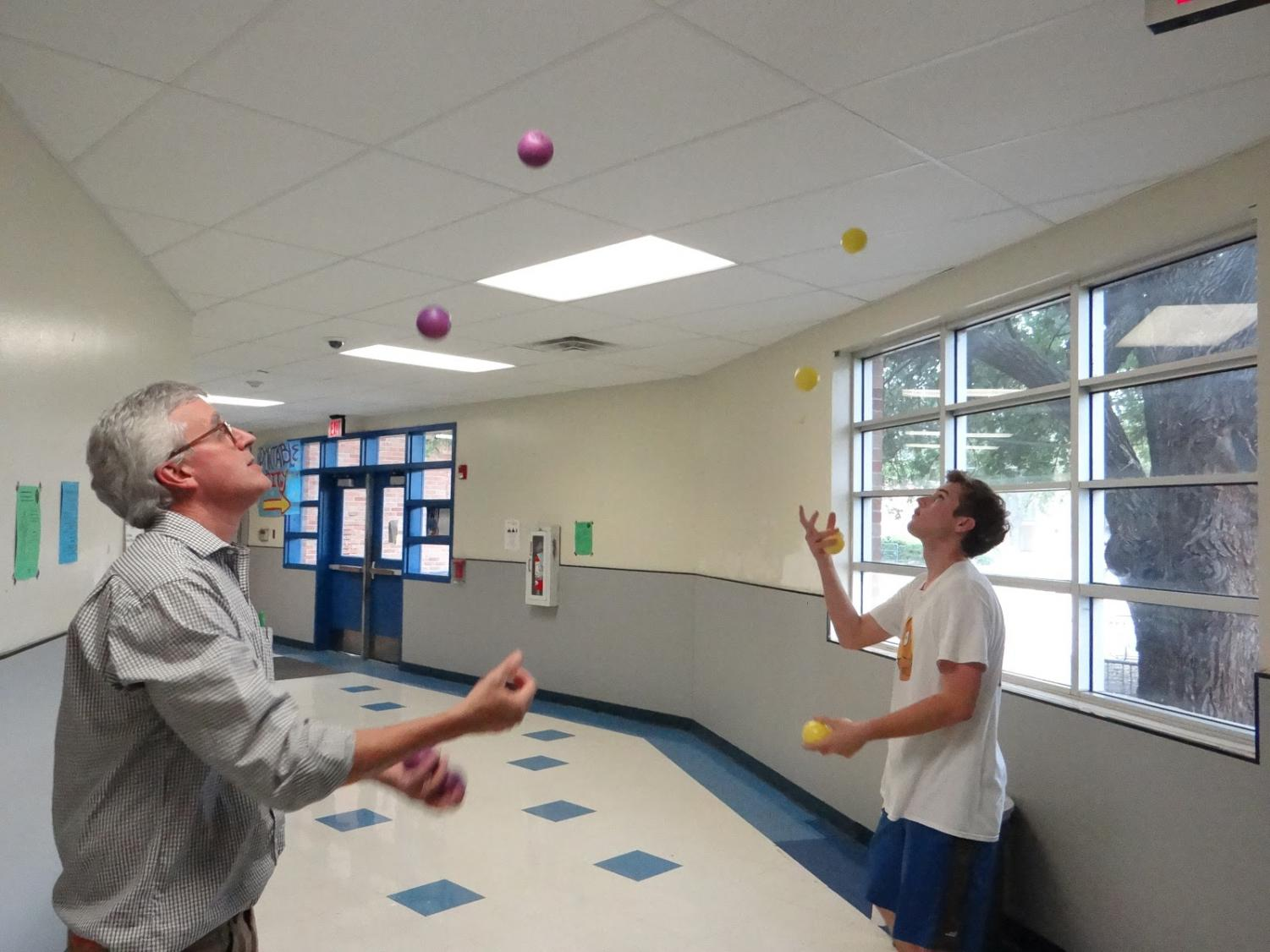 "Mr. Pass and rising senior Will Critendon each juggle five balls simultaneously. Critendon and Pass practice their skills out in the math hall as a part of Juggling Club, a weekly club held on Thursdays helping kids learn how and improve their juggling skills. ""I've been juggling for a couple years now,"" Critendon said. ""The biggest piece of advice I can give to beginners is just to keep practicing even when it gets frustrating."" Photo by Tomas Marrero."