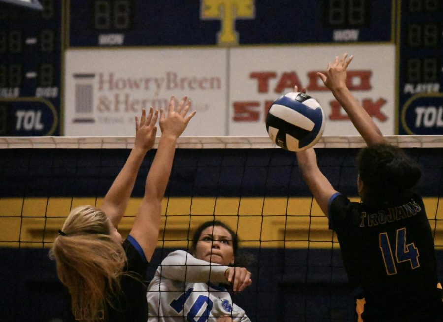 Junior Alexa Fannin spikes the ball between two Anderson defenders during the Knights 3-2 victory over the Trojans at Anderson on Friday night. Fannin, who played for Anderson last year as a sophomore, had eight of the Knights 51 kills for the match. Photo by Bella Russo.