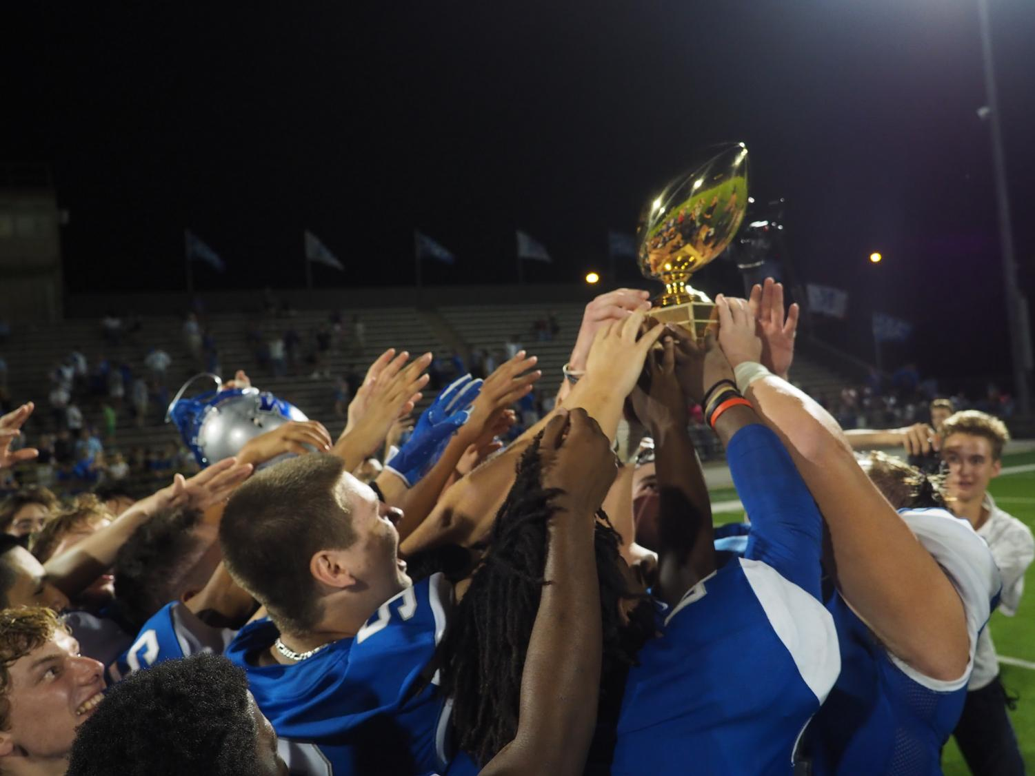 THREEPEAT: The Knights hoist the Taco Shack Trophy after winning the annual game 21-20. Photo by Gregory James