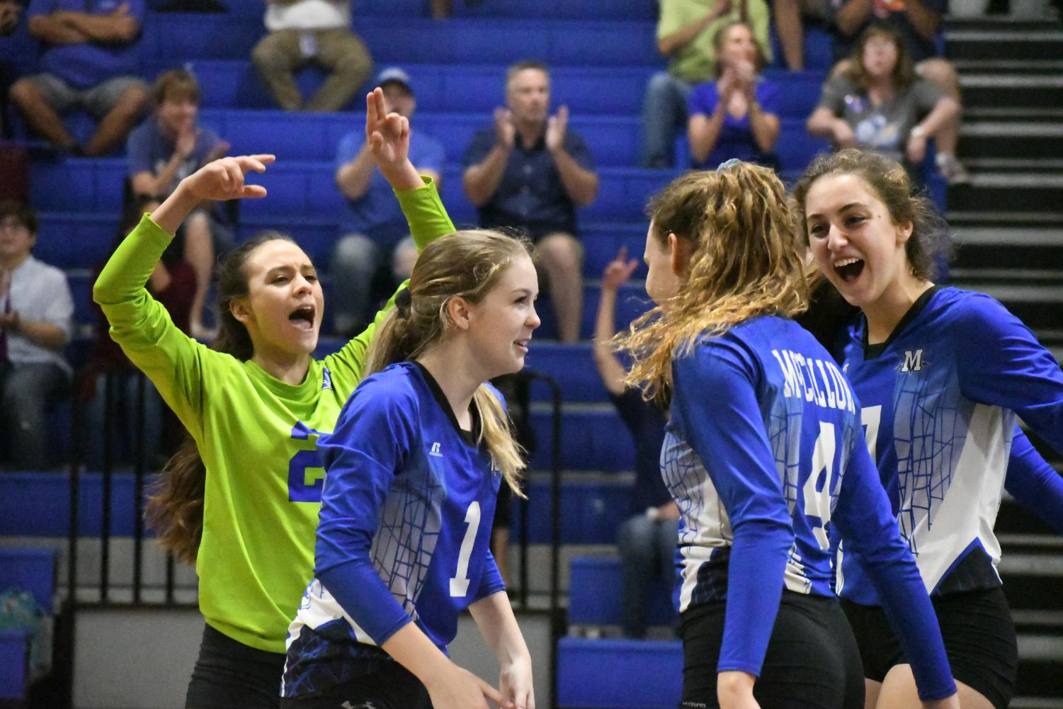 Senior Lindsey Wiley, sophomore Sophia Henderson and junior Liana Smoot celebrate a kill from junior Shaine Rozman.  Photo by Bella Russo.