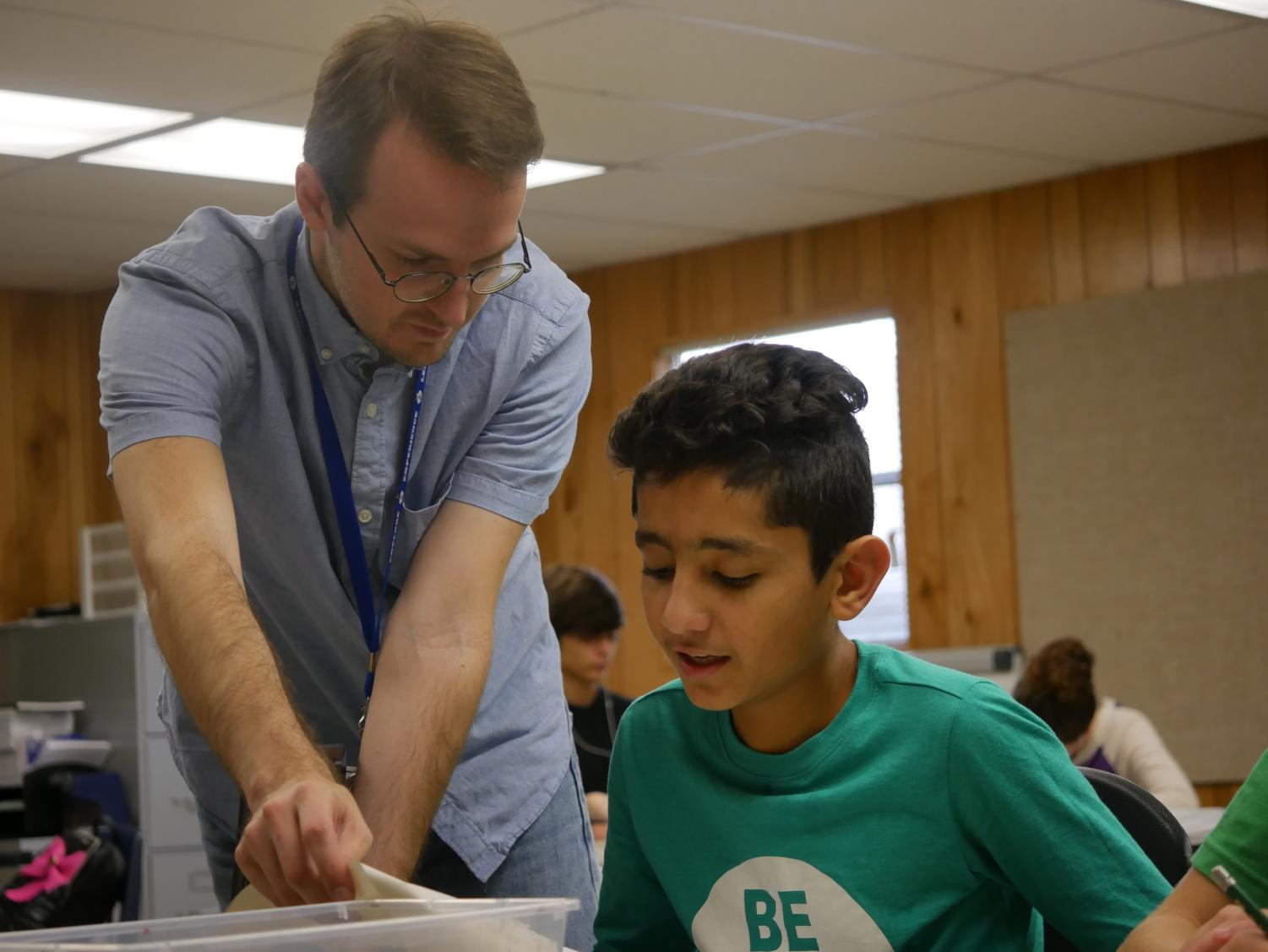 Andrew Cooke works with a student in his first-period Art 1 class.  Cooke was a teacher aide at McCallum last year, and now teaches Commercial Photography 1 and Art 1 full time. He plans to expand into Advanced Commercial Photography next year. Photo by Janssen Transier.