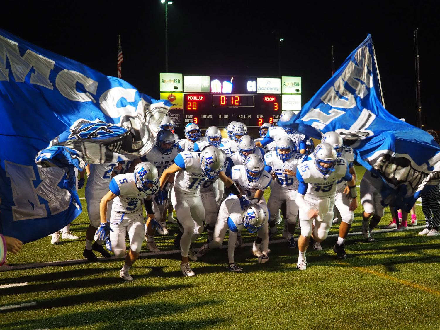 DAWGHOUSE: Varsity football players charge out of the McCallum banner after halftime, leading the Reagan Raiders 28-3. Photo by Gregory James