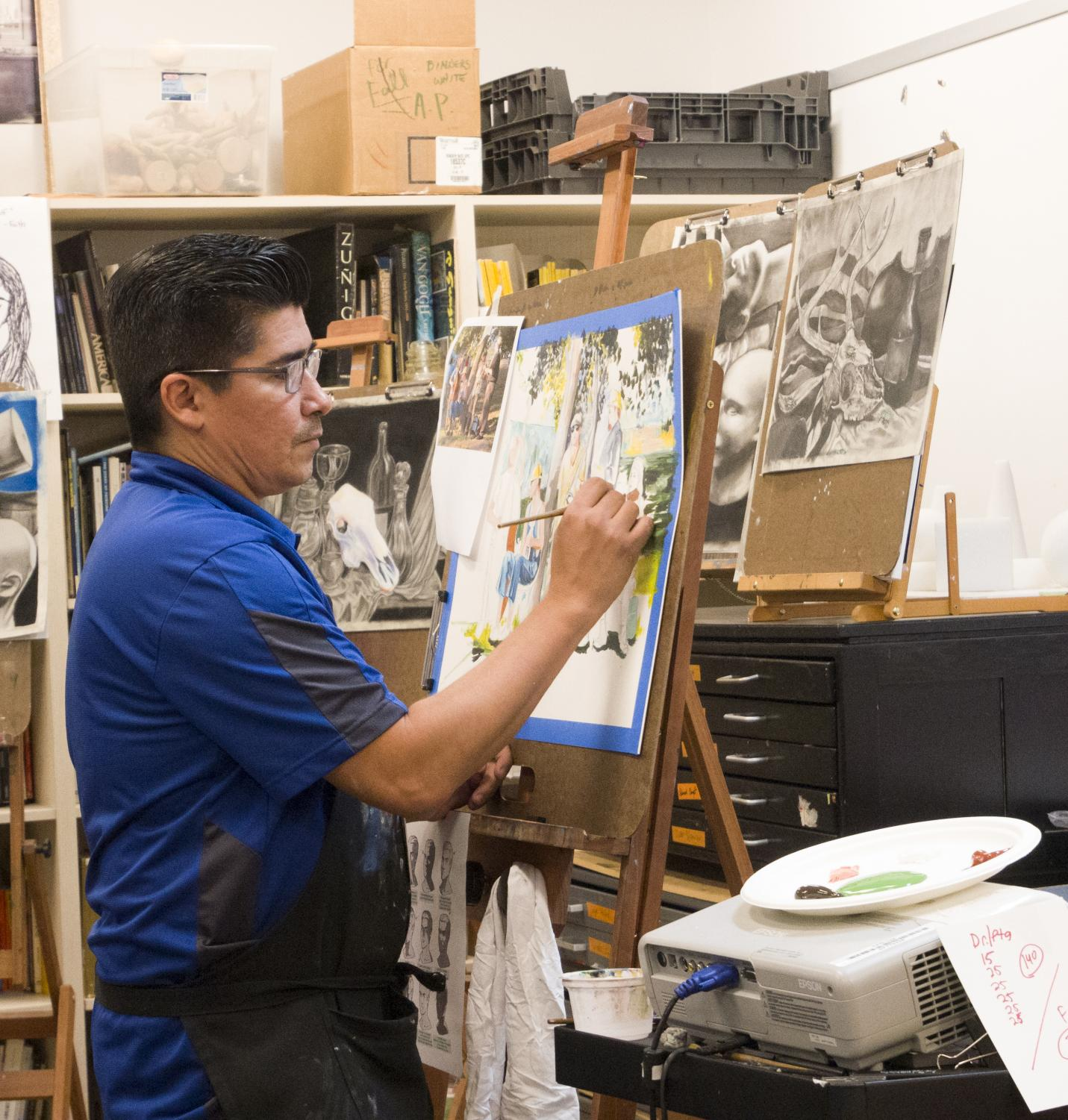 "Mr. Martinez paints for the painting students in his first period classes. The class contains students from drawing II, drawing III and painting III spread throughout the room and hallway. ""[This is] why we do stacked classes,"" Martinez said. ""So that students have choices about where they can go at different periods during the day."" Photo by Kristen Tibbetts."