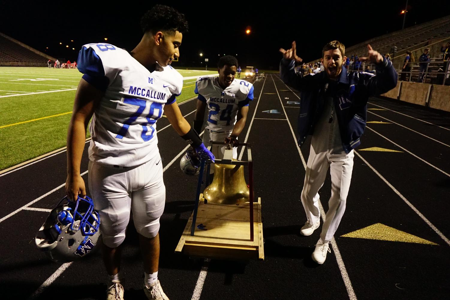 Sophomore Charlie Pecina and junior Caleb Brown wheel the bell towards the team bus after the Knight 63-0 win over the Travis Rebels on Friday. The win marks the 19th time the Knights have taken home the bell in the past 20 years. Photo by Caleb Melville.