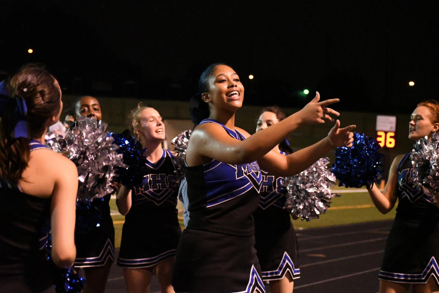 "Surrounded by her teammates, Naiya Antar leads the crowd in a cheer at the Mac vs. LBJ game. Although Mac lost the game 41-7 and the team had to cheer through a driving rainstorm, Antar says that she has a good time despite the final score and the wet weather. ""To see the crowd going crazy over the football players and then get pumped up when they see us cheer, it's really fun,"" Antar said. Photo by Bella Russo."
