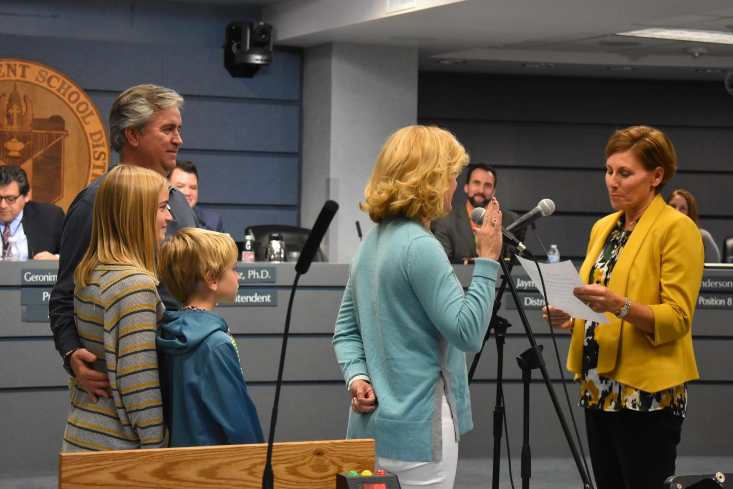 Kristin Ashy, who recently was elected to the Austin ISD Board of Trustees representing District 4, is sworn in by exiting District 4 representative Julie Cowan while her husband and children watch from behind. Photo by Olivia Watts.