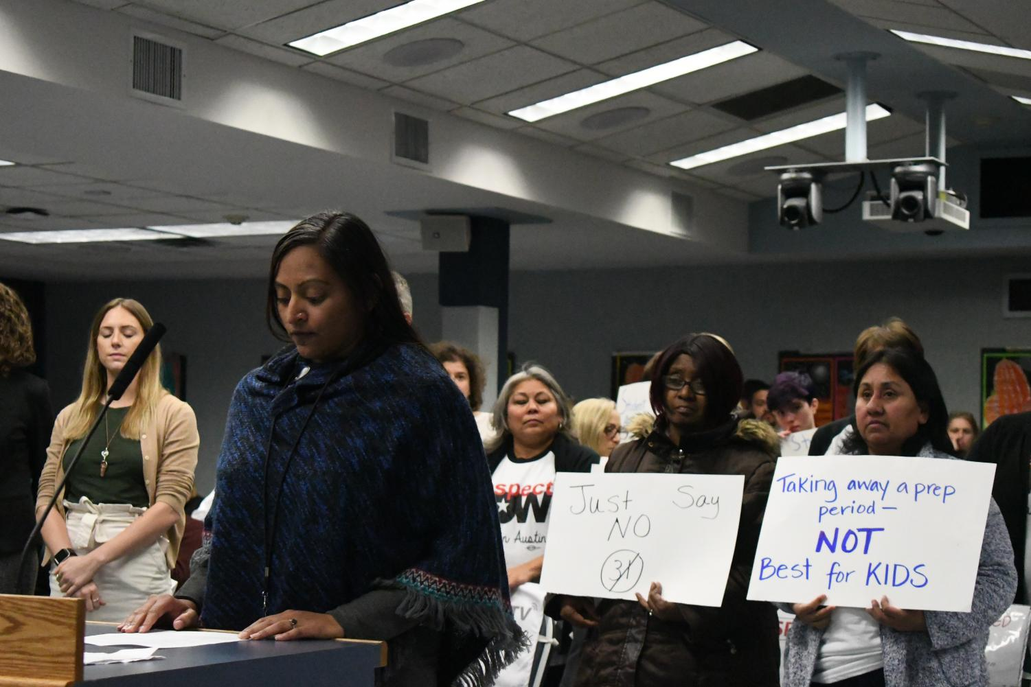 Those in protest of the potential budget for the 2019 school year hold signs during public comments directed at the school board trustees at a Nov. 26 meeting.