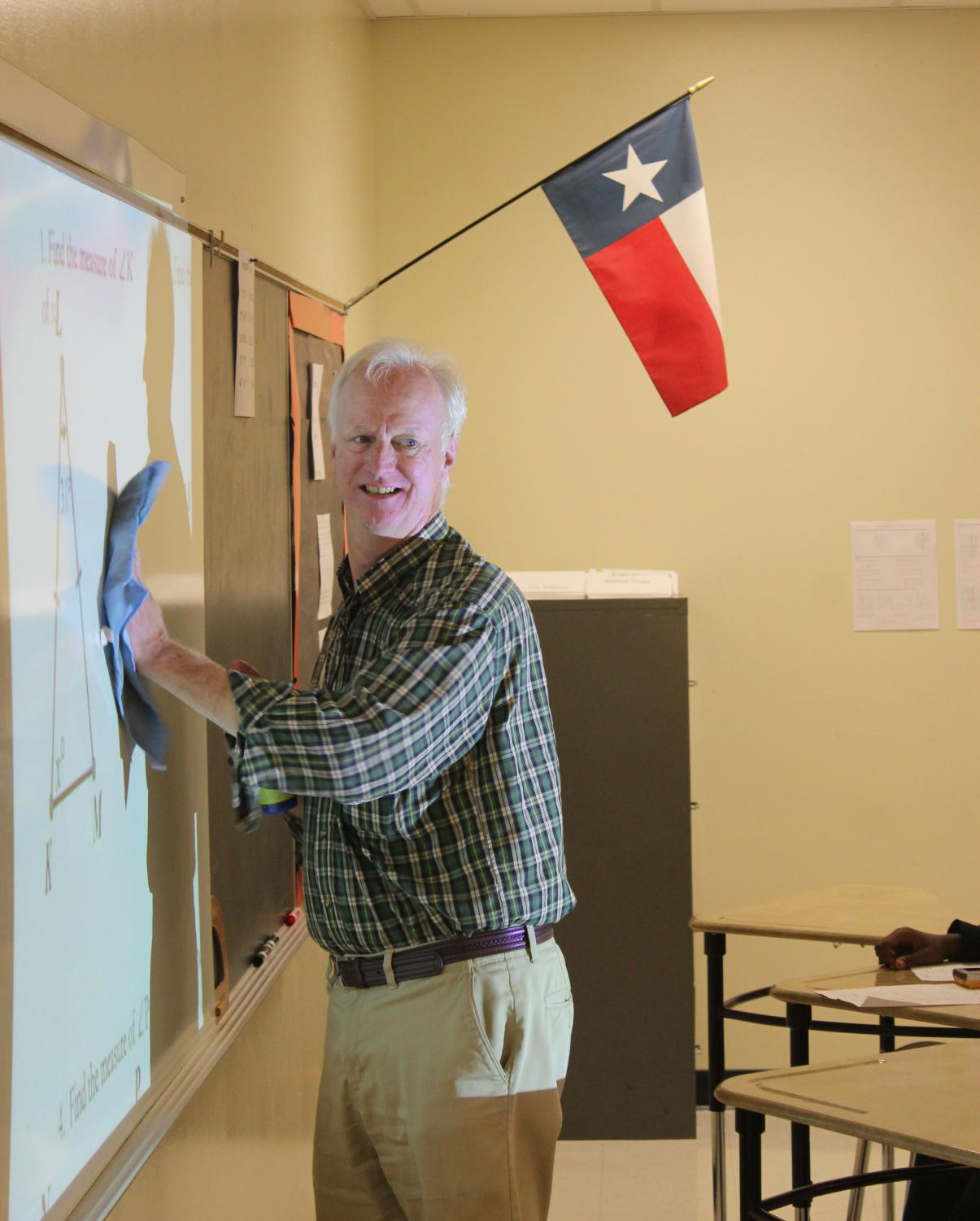 """Mr. Pew finishes demonstrating something on the board. """"In students, I greatly admire courage and willingness to try something."""""""