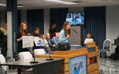 Williams Elementary School teacher Julianne Hart speaks to the board of trustees about her concerns of the lack of security in her school as supporters stand behind her with signs. Williams Elementary doesn't have proper walls separating the classrooms, enough safe places for students in the case of an emergency, or enough staff to supervise recess safely. Photo by Elisha Scott.