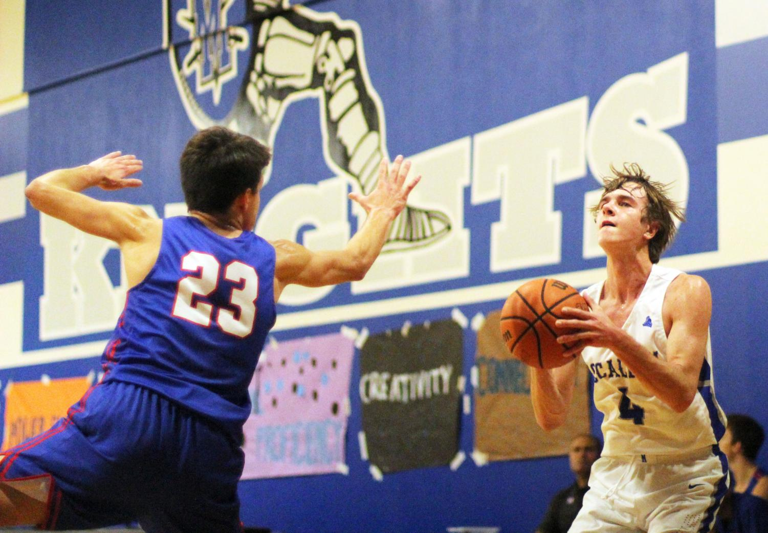 "Junior Sam Werkenthin sets up a shot during McCallum's 56-47 loss to Hays on Nov. 13 at home. Shooting is something Werkenthin has done a lot of this year as he is one of only two returning players from last year's varsity team. ""This year my role has definitely changed. Since me and Norman are the only [players] who have experience playing varsity, [my role is to be] a scorer and a leader."" Photo by Risa Darlington-Horta."