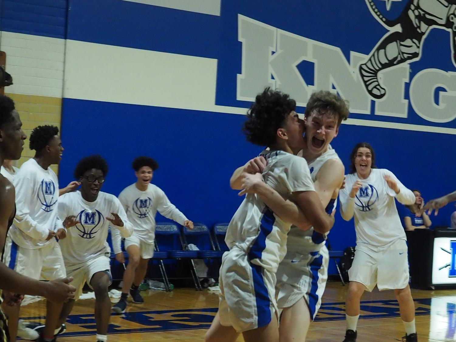 Rob Wade celebrates with teammate Albert Garza after sinking the game-winning shot on a put back as the second overtime period expired. It was the Knights' third shot on the game's final possession, and it dropped through the basket after the buzzer sounded while the ball was still in midair.