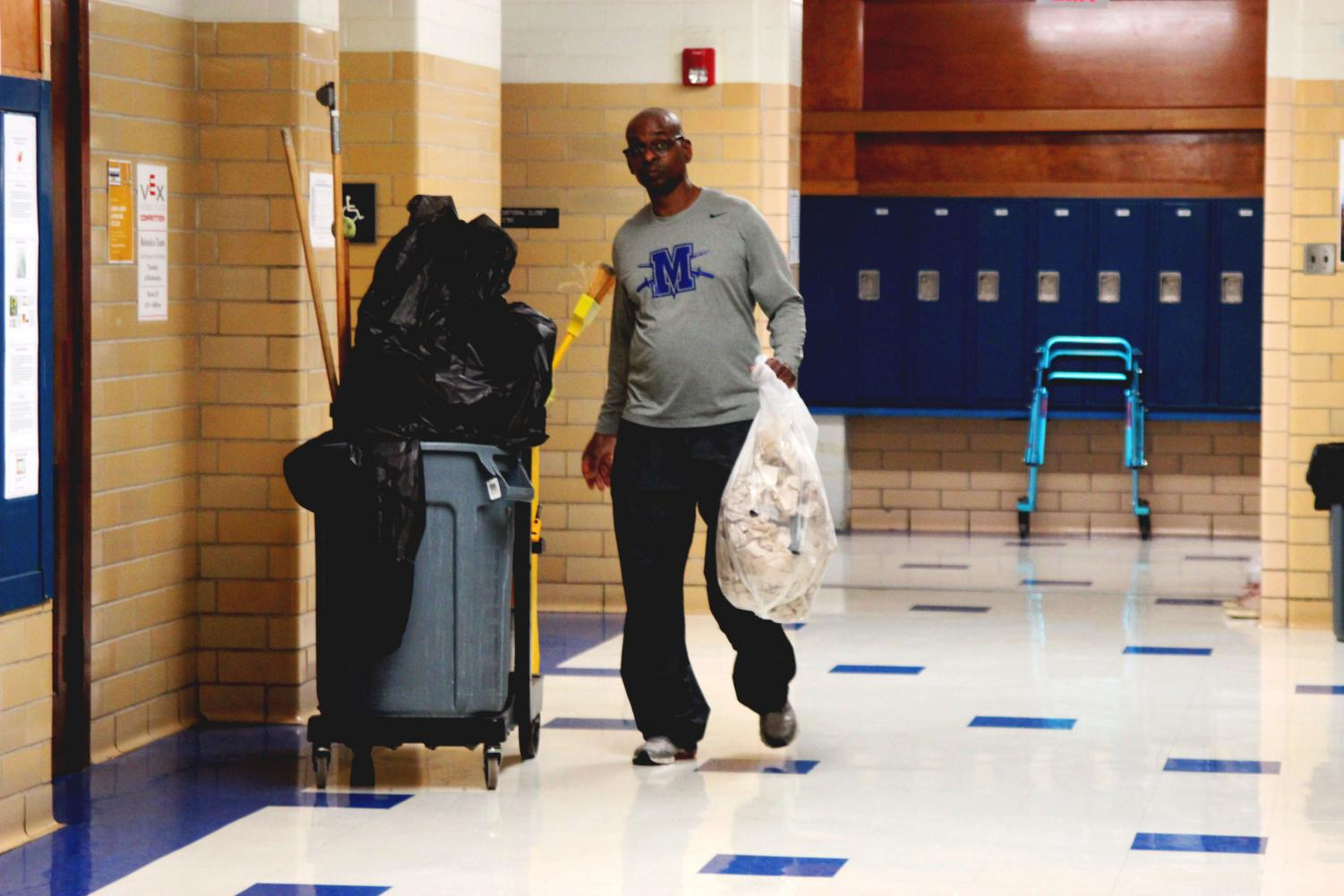 "A HARD DAY'S KNIGHT: Working hard to keep McCallum clean, janitor Kenneth Sterling takes out the trash from the boys bathroom. After finishing the boys bathroom, he cleaned the science hall. ""I never decided to [be a custodian] initially,"