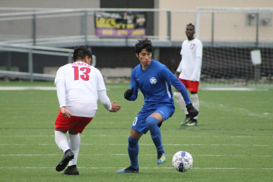 """DRAWING LESSONS: Senior Adrian Martinez dribbles past an opposing Travis player. The boys varsity soccer team played Travis to a 2-2 draw Saturday at House Park. Lucas Ramos De Barros scored (assisted by Marcel Lopez-Reed) as did Anthony Bataille (assisted by Luis Auyero). """"The team played well,"""" fellow varsity player Jimmy Walker said, """"but we need to work on maintaining and finishing the game."""" The team has earned three draws and lost once in its last four."""