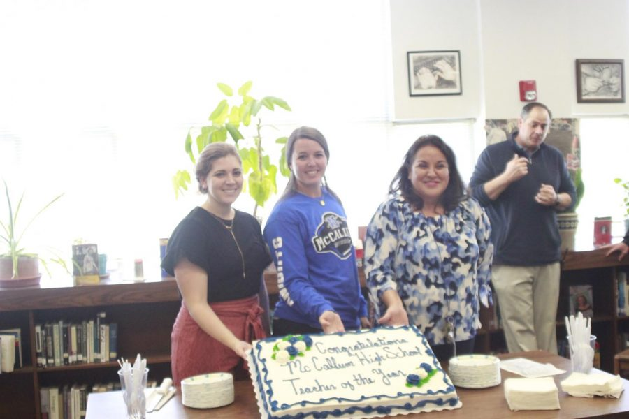 Teacher of the Year finalists Marian Baughman, Stephanie Watson and Juana Gun pose with the celebratory cake that fortuitously matches the colors on Gun's blouse. Moments later, assistant principal Andy Baxa announced that the faculty had selected Gun as the 2019 McCallum Teacher of the Year. Photo by Scarlett Houser.
