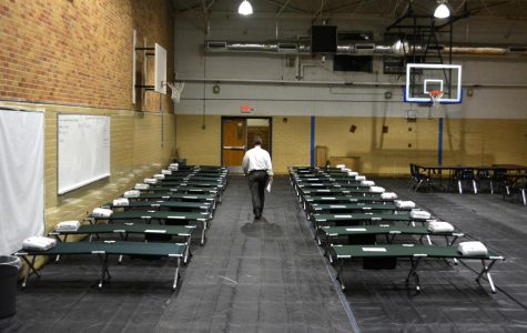 """SHELTER IN PLACE: Principal Mike Garrison walks through the rows of cots as McCallum prepared to become a shelter for Red Cross volunteers on Aug. 29, 2017. The volunteers stayed in the gym for two days before relocating to the Great Hills Baptist Church. """"The volunteers got here, and two days later, poof, they're gone,"""" Garrison said. """"I wanted to make sure it was nothing we did, and it wasn't. They were very nice, they complimented us, they said McCallum was very helpful and flexible, but the Red Cross just came up with another plan."""" Photo by Dave Winter."""