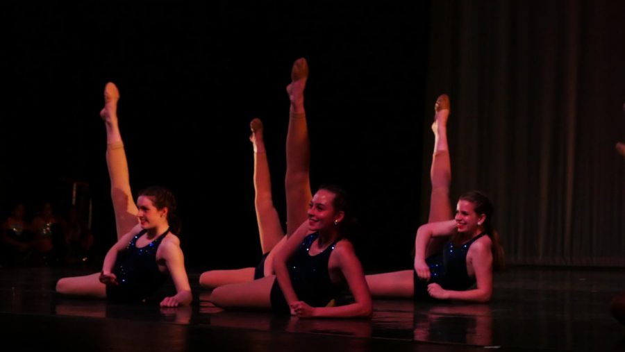 """A LEG UP: Smiling brightly, Amelia Paul, Sydney Buford, and Ella Irwin perform their junior dance — a recreation of the pep rally performance to """"Born this Way"""" by Lady Gaga. Each grade level was featured in their own showcase dance, alongside mass group dances and senior solos. """"Working in a small group let us show off our skills in a fun way,"""" Buford said. Photo by Madelynn Niles."""