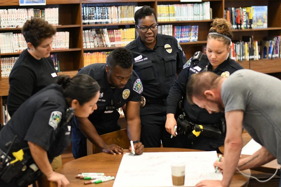 Austin+Police+Department+officers+work+together+to+respond+to+a+poster+activity.+The+roundtable+participants+wrote+down+their+perceptions+of+teenagers+and+police+officers+and+then+came+together+to+discuss+those+perceptions.+Photo+by+Bella+Russo.