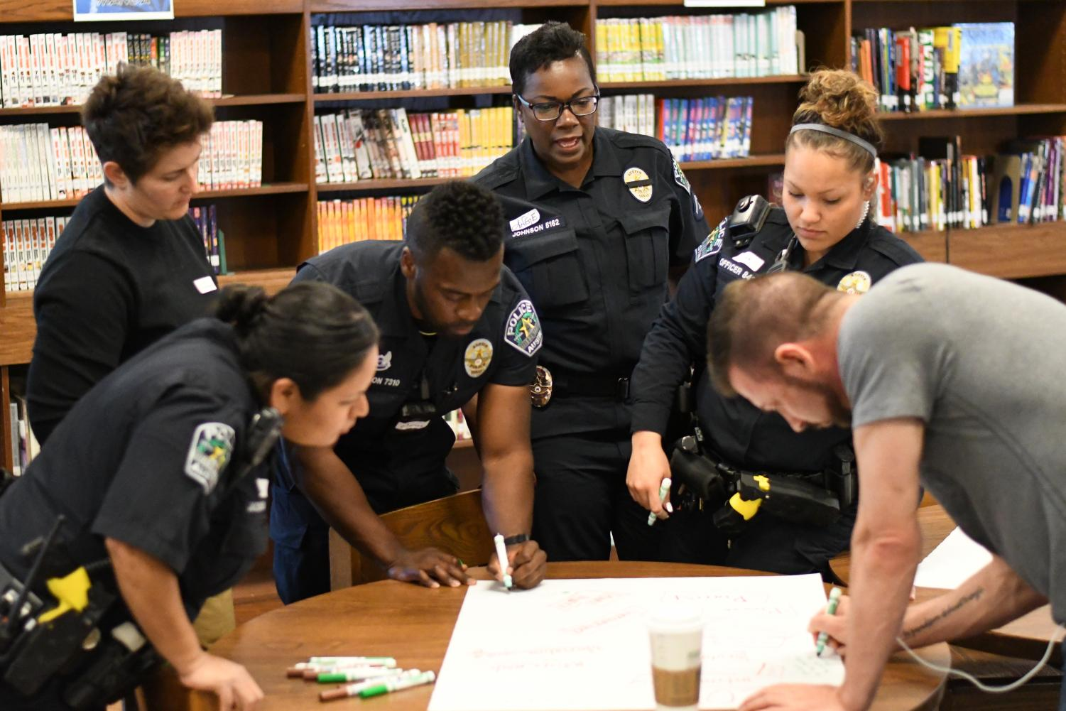 Austin Police Department officers work together to respond to a poster activity. The roundtable participants wrote down their perceptions of teenagers and police officers and then came together to discuss those perceptions. Photo by Bella Russo.