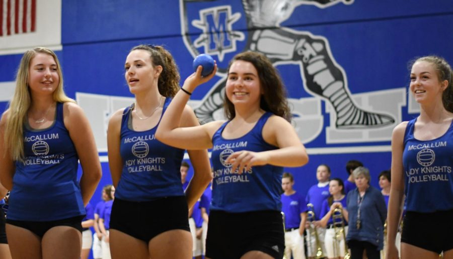 Junior Bridget Russo tosses a souvenir volleyball into the stands during the Back to Mac community pep rally last Wednesday.