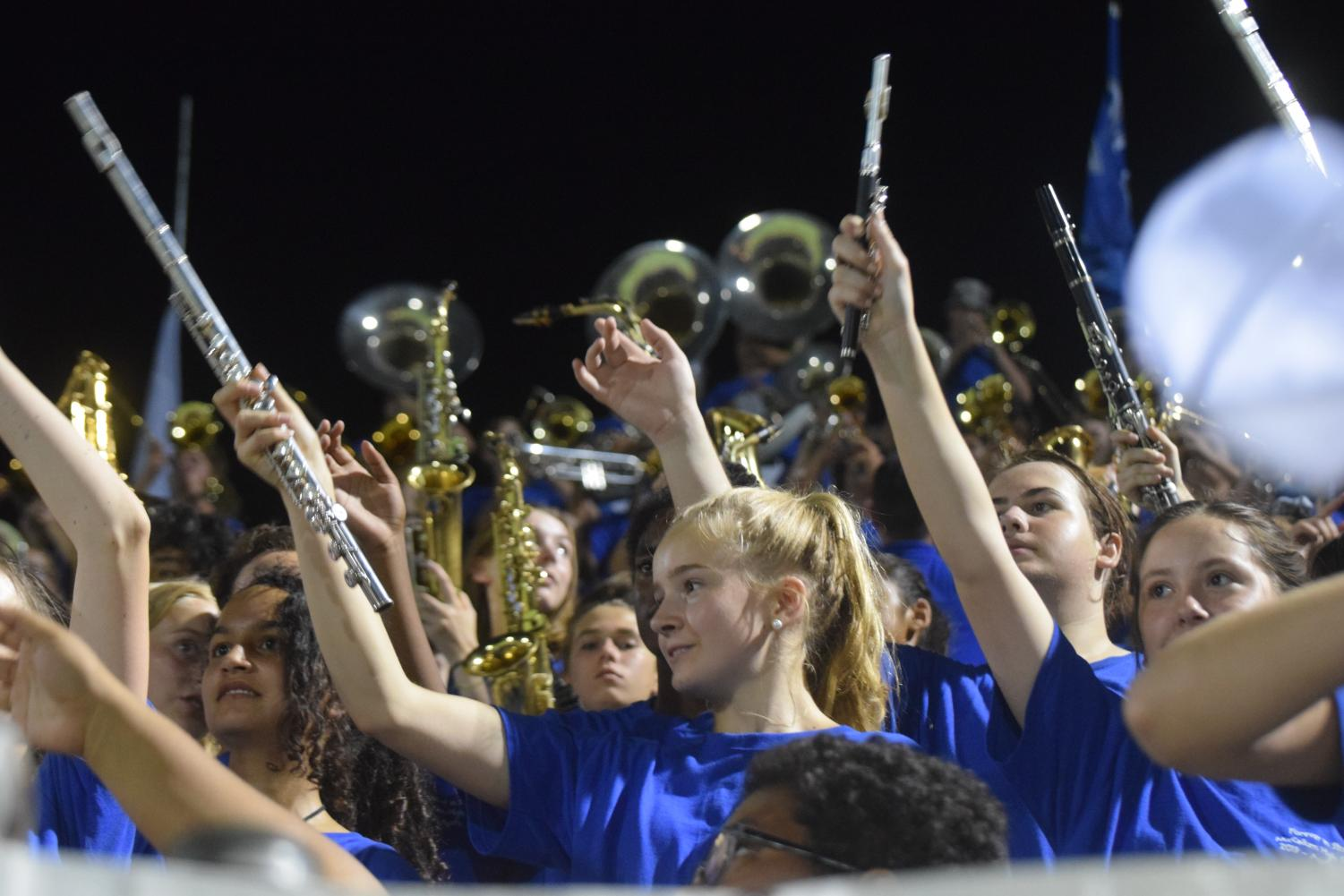 "Ekelin smiles as she waves her flute during a ""brass jam"" in the stands of House Park stadium. Ekelin stated that her experience at Taco Shack has been her favorite one yet. ""I didn't understand most of it, but it was really fun to watch,"" she said. ""I just screamed when everyone else screamed."""