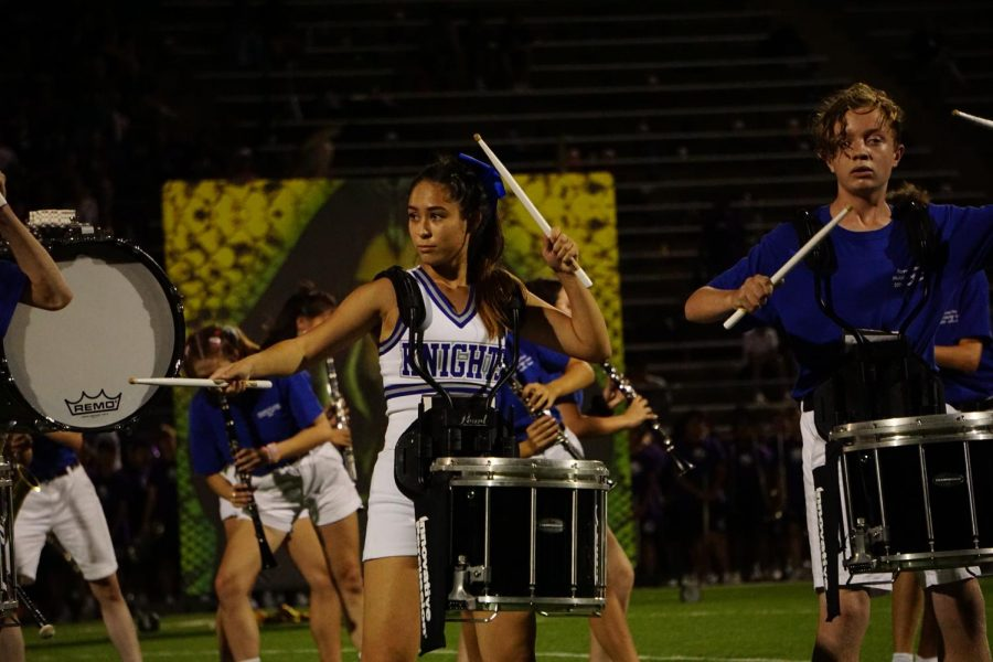 """Collins strikes a pose as part of the 2019 marching show, """"Forever in Stone,"""" at the LBJ football game on Sept. 19 . Both girls get """"no down time"""" at the games, as Crist puts it, because of the quick switches between cheer and band performances."""