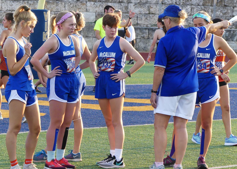 Coach Susan Ashton talks to girls varsity cross-country runners, giving them advice before their race on Sept. 14 at the Vista Ridge Invitational meet. Photo by Thomas Melina Raab.