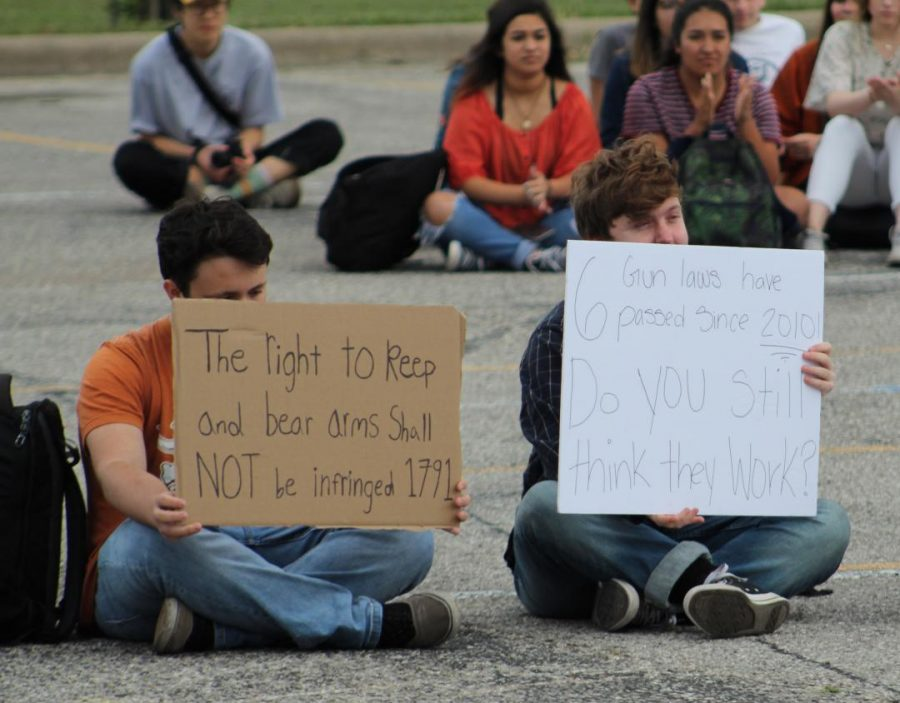 """Defending the rights of gun owners at the McCallum walkout in support of stronger gun control legislation on April 20, 2018, then senior Owen Myers (not pictured) joined three other McCallum students, Diego Winfree and Jack Schenkman (shown here) and Gabriel Guitierrez in silently counter-protesting at the rally in the parking lot. """"I believe in the Second Amendment since it was instituted in the beginning of this country, Myers said. I obviously don't believe in fully automatic weapons. They aren't legal anyways. I'm pro-rifle, pro-gun and I'm pro Constitution."""" Photo by Kien Johnson."""
