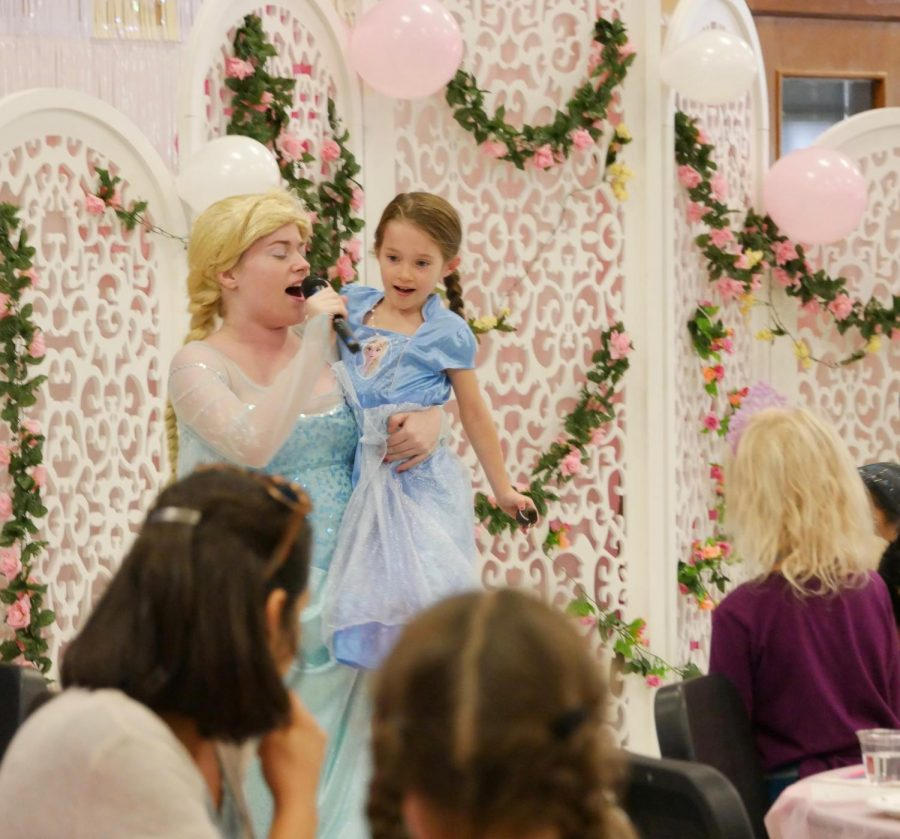 "SEEING DOUBLE: Senior Maryanna Tollemache and another, smaller Princess Elsa sing ""Let it Go"" for a crowd of other princesses and their parents. Due to the wireless microphones used this year, Tollemache and the other actors were able to better interact with the kids. ""It's always unique due to the kids who come and the cast,"" Tollemache said. ""I love seeing the kids get excited. They would all circle around and begin to sing with me and I just loved seeing how happy they are!"""
