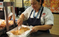 "HOT LUNCH HERO: Ruth Villarreal serves warm bread to students. Villarreal takes pride in her work and is well-known for her kindness in the lunch line. ""My favorite part of my job is serving to the future,"" Villarreal said. ""You are my future."" Photo by Lucy Marco."