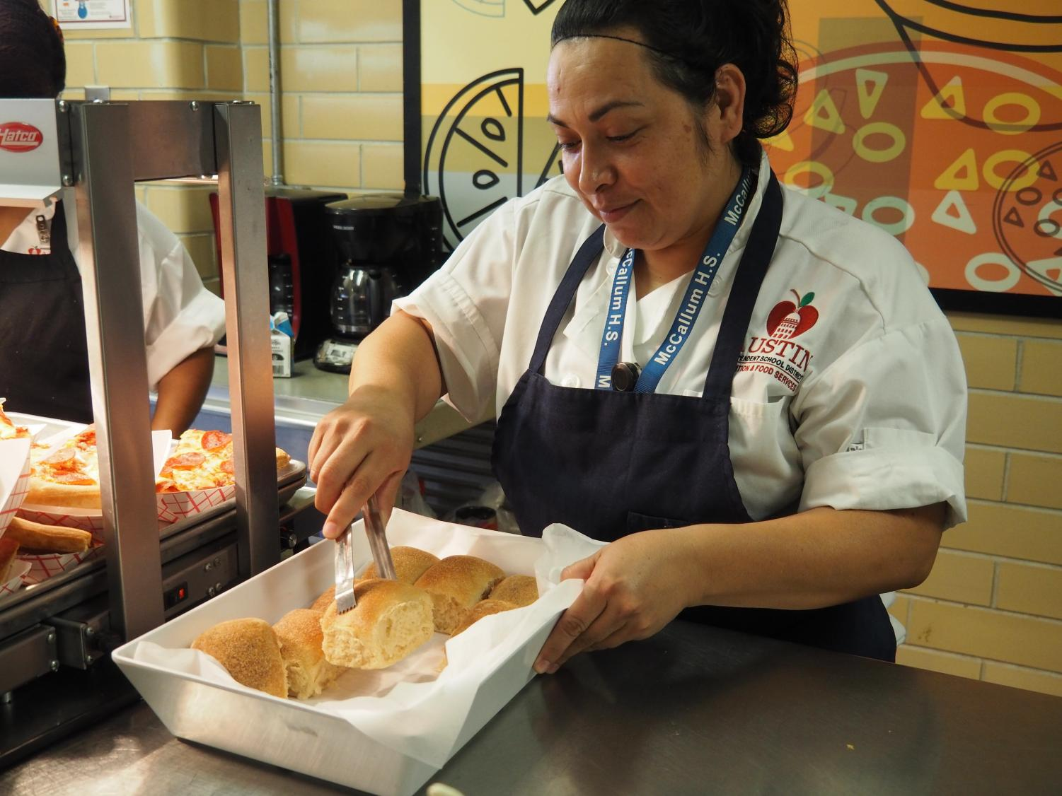 """HOT LUNCH HERO: Ruth Villarreal serves warm bread to students. Villarreal takes pride in her work and is well-known for her kindness in the lunch line. """"My favorite part of my job is serving to the future,"""" Villarreal said. """"You are my future."""" Photo by Lucy Marco."""