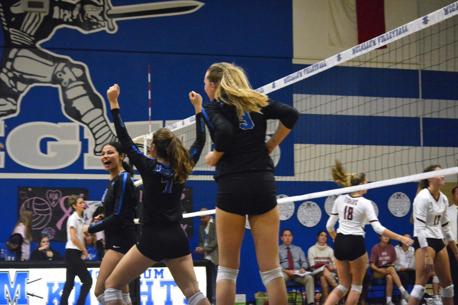 Senior varsity volleyball player Alexa Fannin celebrates winning a point with teammates Shaine Rozman and Grace Werkenthin during the Knights' home loss to Dripping Springs on Oct. 25. The Knights came up short but took solace in how well they placed against such a quality opponent.