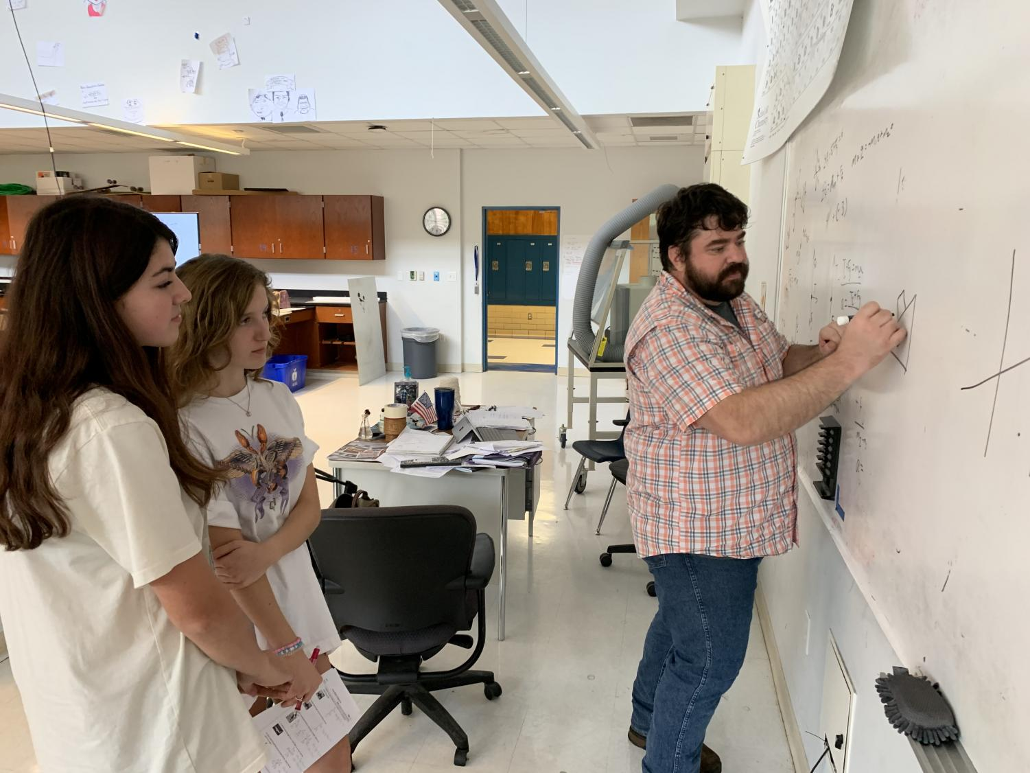 Black and White: Physics teacher Nicholas Koslan draws a free body diagram for juniors Lily Prather and Lily Wilson on his class whiteboard. Koslan, a Physics I and II teacher, previously worked with researchers studying the affects of certain chemicals on brain tumors. Photos by Tomas Marrero