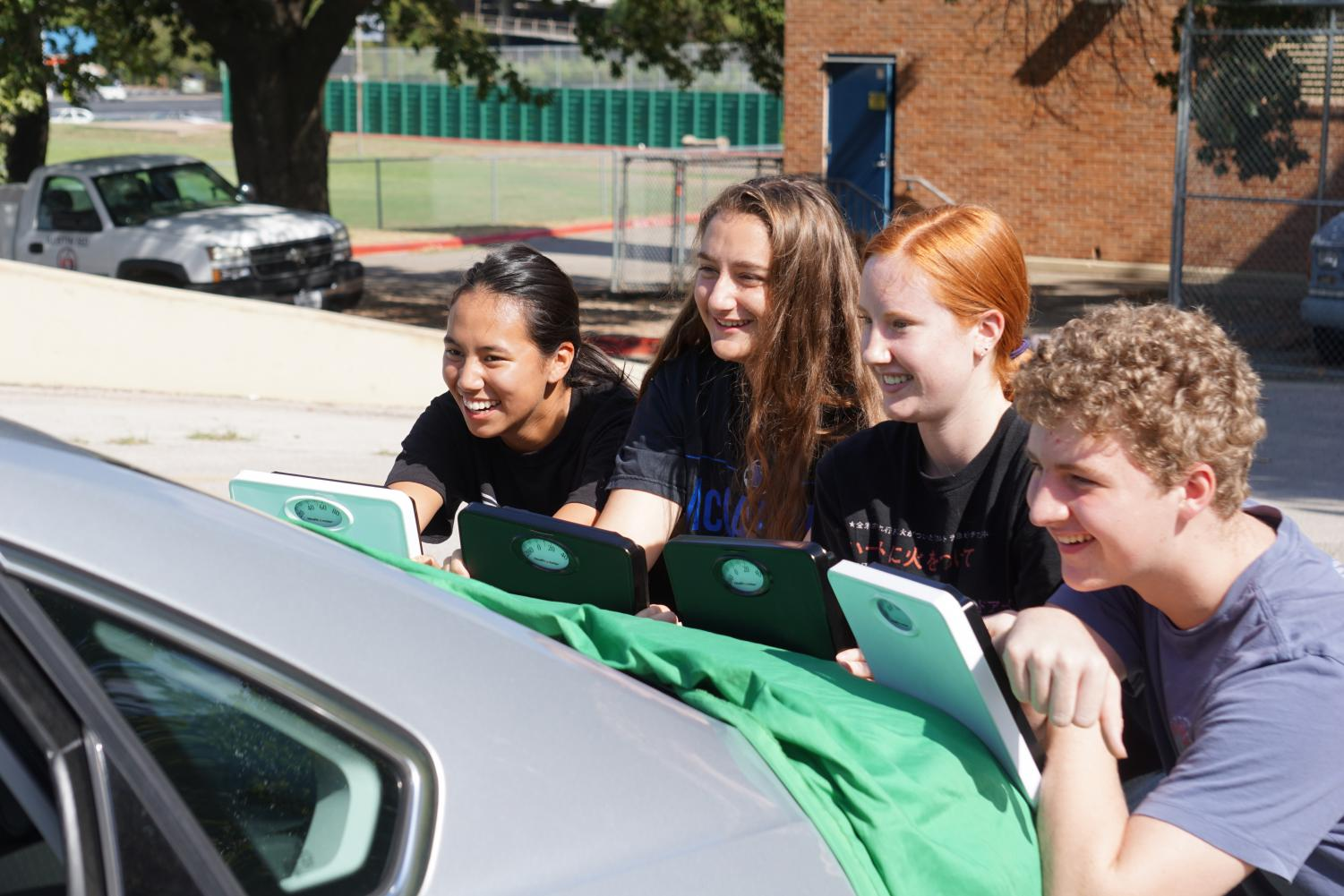 """AP PHYSICS, A WEIGHTY SUBJECT: Juniors Hannah Zuniga, Lindsey Plotkin, Darian Dieterich and Tres Tanner complete a hands-on lab, in which the task was to use the skills they'd learned in trigonometry to solve for the mass of the car. """"The lab was really interesting,"""" Tanner said. """"Physics is a fun class; I will be taking the AP test."""" Photo by Bella Kisler."""