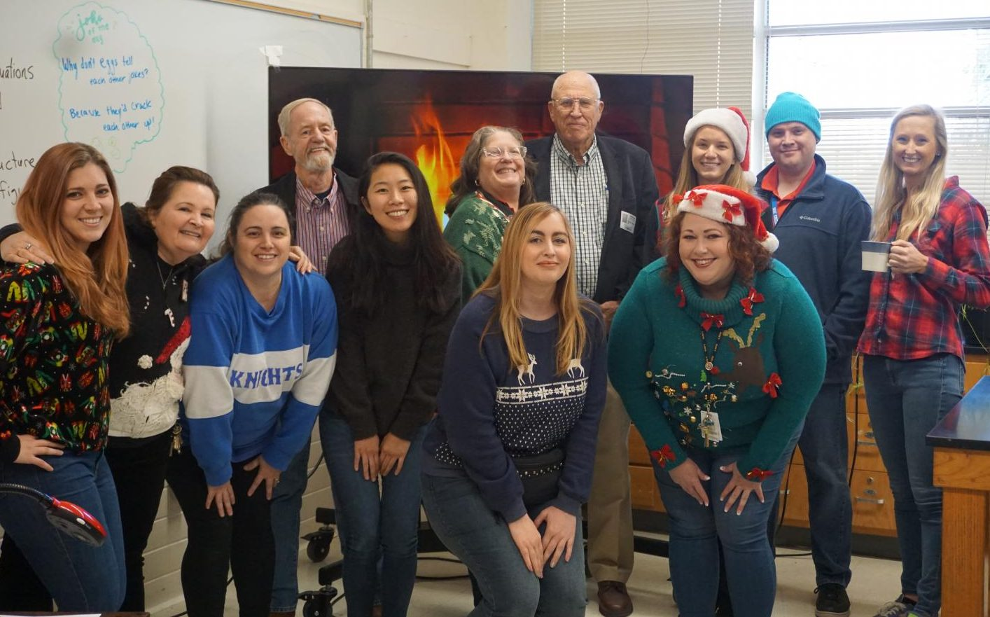 The science department, including former science teachers Robert Lehman and Richard Whisennand, pose for a group photo at the annual department holiday party on Wednesday, Dec. 18, in Mr. Ely's room. Photo by Lindsey Plotkin.
