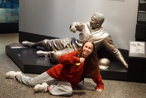 Sophomore Risa Darlington-Horta slides safely in front of a statue of Jackie Robinson at the African-American History Museum on Sunday, the same day she learned that she had earned an excellent rating in portrait photography in the JEA National Student Media Contest.
