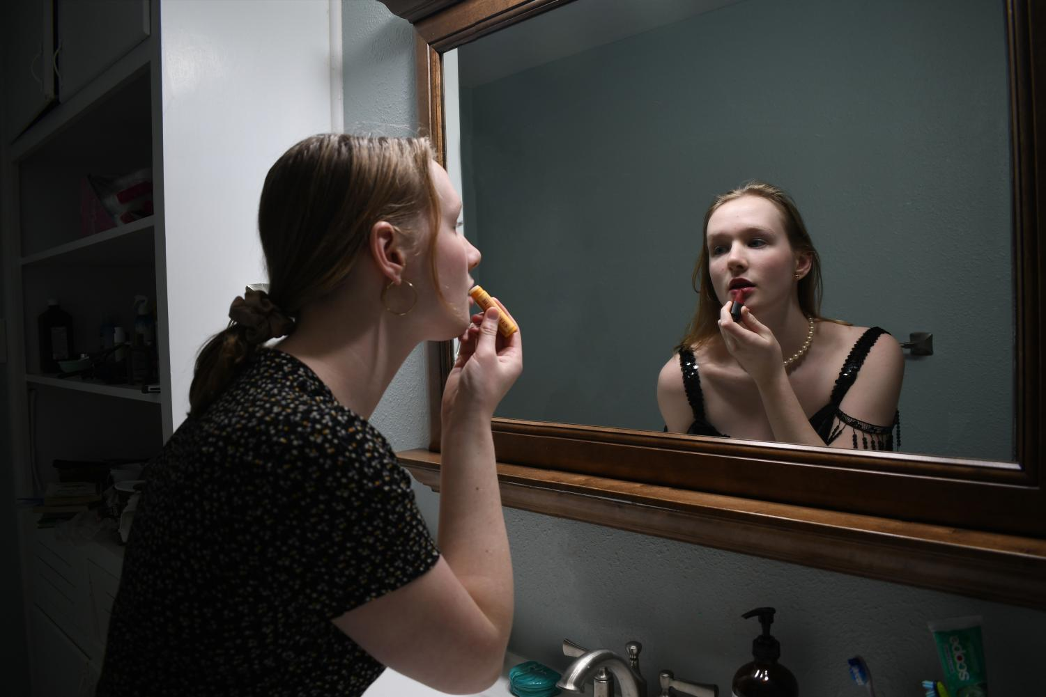 THROUGH THE LOOKING GLASS: Junior Ellen Fox looks upon on a Roaring 1920s reflection of herself in the mirror. The reflection flaunts the staples of  the time period: a flapper dress, a pearl necklace, and red lipstick. In the modern 2020's version, she wears modern equivalents; a Madewell dress, hoops, a scrunchie and Chapstick. Original photos and digital illustration by Ellen Fox.